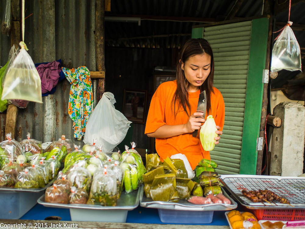 "04 FEBRUARY 2015 - BANGKOK, THAILAND:  A street food vendor grates unripened papaya to make ""som tam"" or Thai papaya salad, in central Bangkok. After months of relative calm following the May 2014 coup, tensions are increasing in Bangkok. The military backed junta has threatened to crack down on anyone who opposes the government. Relations with the United States have deteriorated after Daniel Russel, the US Assistant Secretary of State for Asian and Pacific Affairs, said that normalization of relations between Thailand and the US would depend on the restoration of a credible democratically elected government in Thailand.   PHOTO BY JACK KURTZ"