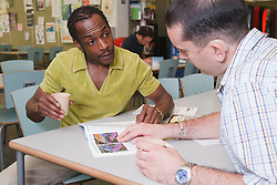 Man with hearing impairment with fellow student in university coffee bar.