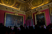 "Tourists crowd in the Salon de Mars in the King's Grand Apartment, Versaille, Paris. The choice of this military theme which inspired all the decoration of the salon can be explained by the fact that this large room was originally meant to serve as the guard room for the parade apartment. It was later reserved, at evening soirees, for music and dancing, so that it was commonly known as the ""ballroom"". The court ballets were strictly regulated and required many rehearsals; the princes took part in them, sometimes mixed in with professional dancers."