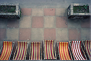 Graphic composition from above of stripped beach chairs and a grid of patio tiles