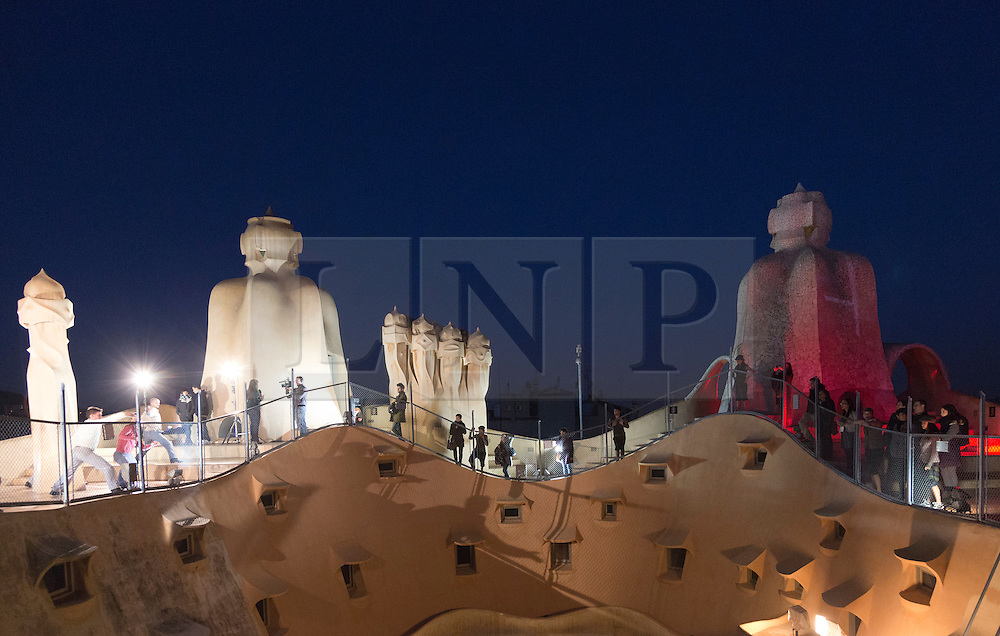 """© Licensed to London News Pictures. 1 December 2012. Barcelona, Spain. Show """"Emocions en moviment"""" on the roof. In 1912, La Pedrera (Casa Mila), Barcelona's iconic landmark by architect Antoni Gaudi was finished  To celebrate 100 years of La Pedrera, Barcelona citizens were treated to a free tour of the building where 150 dancers and musicians performed around every corner and on the roof. Later, images were projected onto the façade of the building with live dancers interacting with them. Photo credit: Bettina Strenske/LNP"""