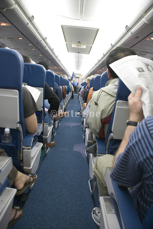 people reading and resting during flight in commercial airplane economy class