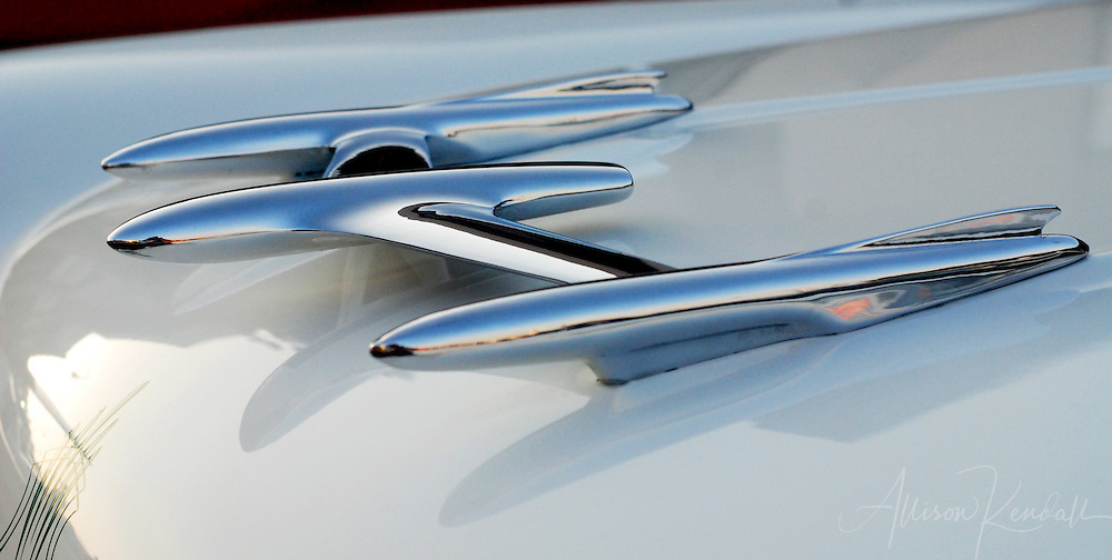 A striking chrome hood ornament glows in evening light at a classic car show
