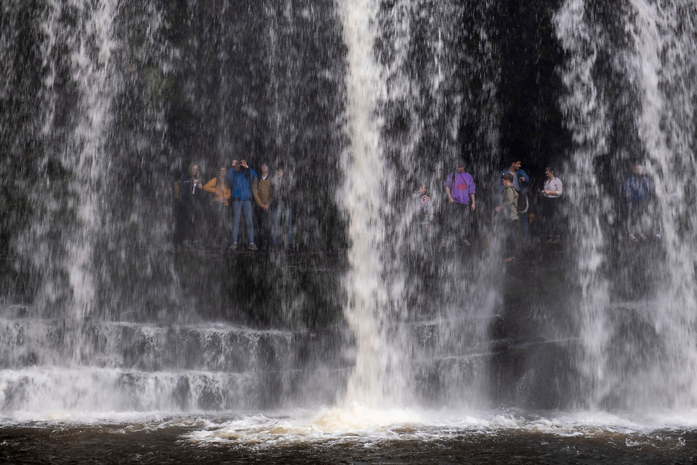 A group of people admire and explore behind the Sgwd Yr Eira Waterfall in the Afon Hepste River in Brecon Beacons Waterfall Country National Park, Wales, Powys, United Kingdom. This waterfall is famous as one of the only waterfalls in Wales that you can walk behind.  (photo by Andrew Aitchison / In pictures via Getty Images)
