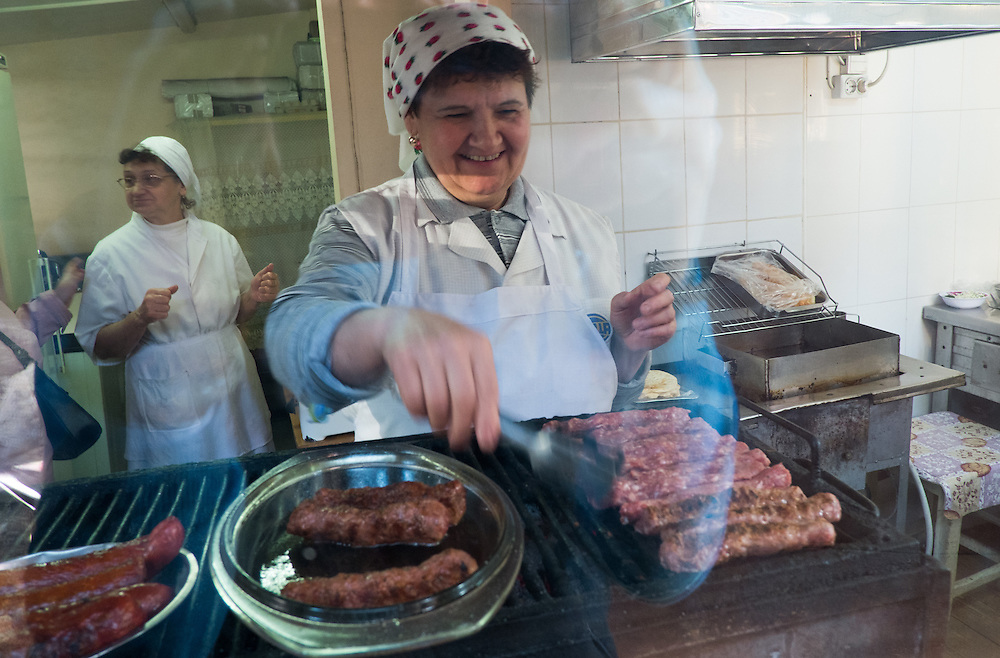 "TIMISOARA, ROMANIA - APRIL 21:  A woman prepares some ""mititei"" (meat sausages) at her stall at the daily market on April 21, 2013 in Timisoara, Romania.  Romania has abandoned a target deadline of 2015 to switch to the single European currency and will now submit to the European Commission a programme on progress towards the adoption of the Euro, which for the first time will not have a target date. (Photo by Marco Secchi/Getty Images)"