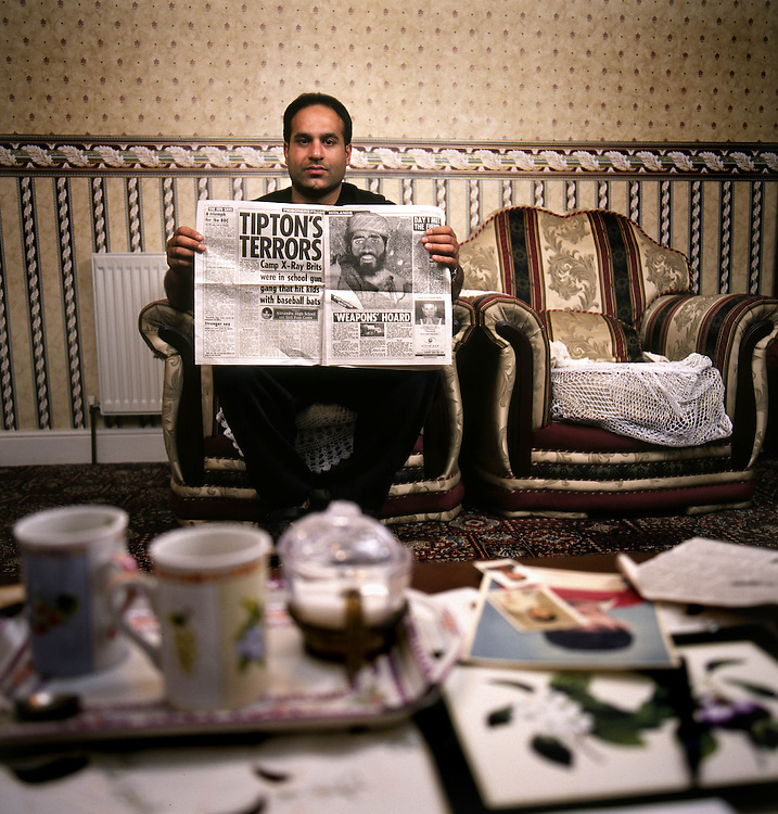 Murtza Rasul, 32, holds a newspaper article that allegedly shows his brother, Shafiq Rasul, with a bullet wound after he was captured in Afghanistan in 2001. Photographed at the family home in Tipton in the East Midlands, UK. Shafiq Rasul was detained by the US at the Guantanamo Bay military base at the edge of Cuba.