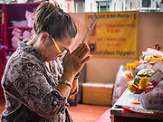 "10 AUGUST 2014 - BANGKOK, THAILAND: A woman prays on the first day of Ghost Month at the Poh Teck Tung Shrine in Bangkok. The seventh month of the Chinese Lunar calendar is called ""Ghost Month"" during which ghosts and spirits, including those of the deceased ancestors, come out from the lower realm. It is common for Chinese people to make merit during the month by burning ""hell money"" and presenting food to the ghosts.    PHOTO BY JACK KURTZ"
