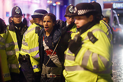 © licensed to London News Pictures. London, UK 01/01/2014. A man being arrested in Leicester Square, London after a fight between revellers who celebrating the New Year at the first hours of 2014. Photo credit: Tolga Akmen/LNP