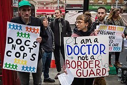 London, UK. 23 October, 2019. NHS doctors and health workers and campaigners from Docs Not Cops hold a vigil outside Royal London Hospital on the second anniversary of the expansion of charging and ID checking across the NHS to highlight the harmful impact of racist Hostile Environment policies in the NHS, to commemorate those who have died and suffered as a result of those policies and to demand an end to all forms of immigration control in the NHS and universal healthcare for all.