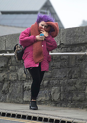 © Licensed to London News Pictures. 09/02/2019. Aberystwyth, UK.  A woman struggles through strong gusts during the tail end of Storm Erik - the first named storm of 2019 - still has enough strength to bring huge waves battering the sea defences at Aberystwyth on the Cardigan Bay coast, West Wales at high  tide this morning. . Photo credit: Keith Morris/LNP