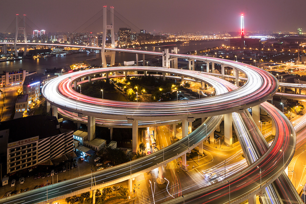China, Shanghai, Overhead view of traffic on highway freeway overpasses stacked in layers at entrance to Nanpu Bridge over Huangpu River