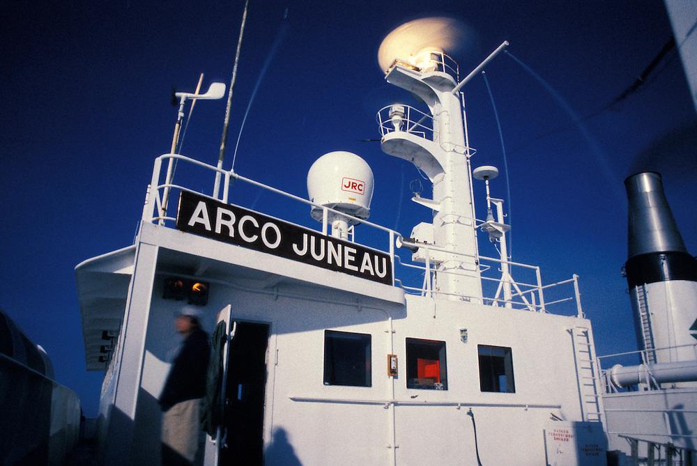 USA, Alaska, Mate on night watch aboard oil tanker under full moon