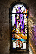 Recent stained glass windows in St Margaret's Chapel, Edinburgh's oldest building, a royal place of peace and prayer. Scotland's royals once knelt to worship in this private chapel. It was built around 1130 by David I and dedicated to his mother Queen Margaret, a member of the English royal family who fled the Norman invasion and married Malcolm III. The decorated chancel arch is original, while other features, such as the stained glass windows, are more recent. In the 1500s, the chapel was used as a gunpowder store and was later given bomb-proof vaulting. Edinburgh is the capital city of Scotland, in Lothian on the Firth of Forth, Scotland, United Kingdom, Europe.