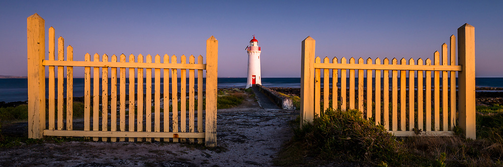 Port Fairy Lighthouse on Griffith Island. The lighthouse is framed by the old fence that marks its entrance.