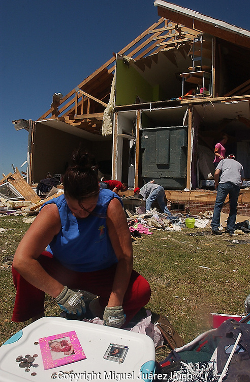 "Rainsville, Alabama: Melanie Sarratt organizes her daughter's photos and sorts change in front of her ruined house. At least seven houses in their subdivision--knicknamed ""Rainbow's End""--where obliterated when one of many tornadoes swept through the area Wednesday. At least 32 people are confirmed dead in Dekalb County in northeastern Alabama. The Sarratt family survived. (PHOTO: MIGUEL JUAREZ LUGO)"