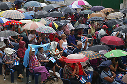 Crowd of spectators in the rain at revolutionary meeting; Havana; Cuba,