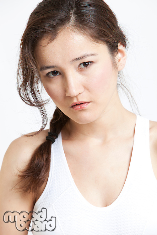 Portrait of beautiful Asian woman in white tank top against white background