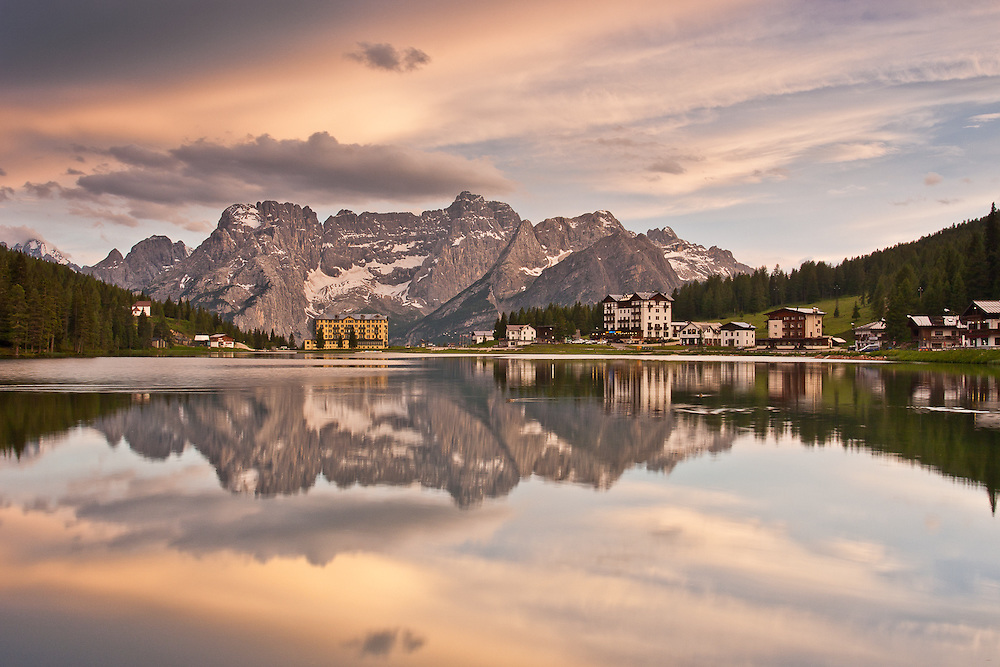 Misurina Hotel stands against the backdrop of the mountains, which in turn are reflected on this well-known lake in the Dolomiti
