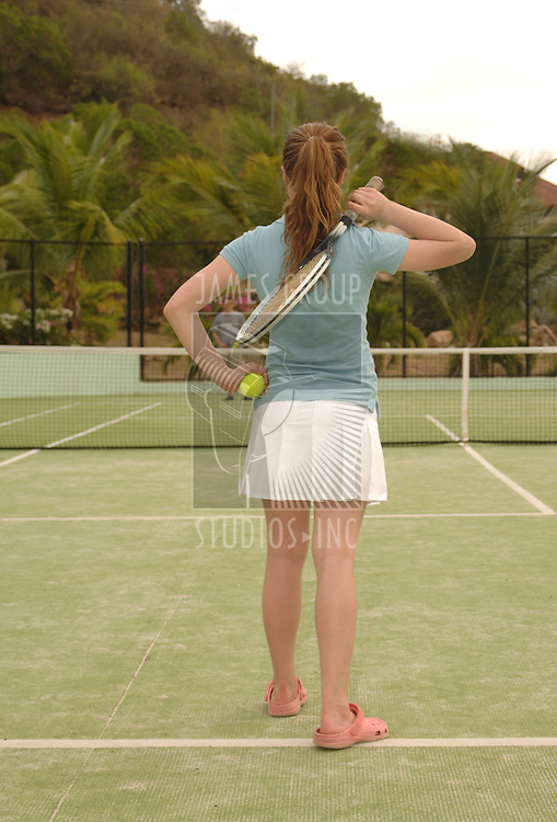 Girl ready to serve on an outdoor tennis court