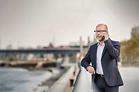Portrait of mature businessman standing while talking on smartphone