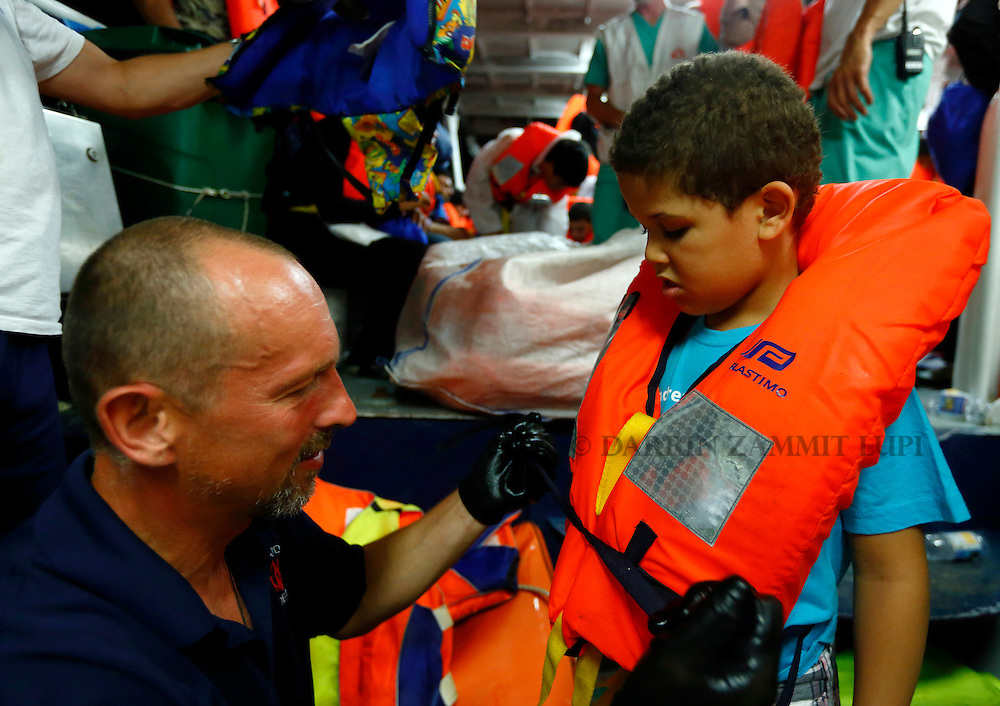 A crewman fits a life jacket onto a migrant child on the Migrant Offshore Aid Station (MOAS) ship MV Phoenix before migrants were transferred to the Norwegian ship Siem Pilot off the coast of Libya August 6, 2015.  An estimated 700 migrants on an overloaded wooden boat were rescued 10.5 miles (16 kilometres) off the coast of Libya by the international non-governmental organisations Medecins san Frontiere (MSF) and MOAS without loss of life on Thursday afternoon, according to MSF and MOAS, a day after more than 200 migrants are feared to have drowned in the latest Mediterranean boat tragedy after rescuers saved over 370 people from a capsized boat thought to be carrying 600.<br /> REUTERS/Darrin Zammit Lupi <br /> MALTA OUT. NO COMMERCIAL OR EDITORIAL SALES IN MALTA