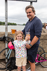 "© Licensed to London News Pictures. 04/07/2020. London, UK. Rory Odell and his daughter Primrose 5 from Barnes enjoy a pint of beer and an orange juice along the River Thames at Barnes in South West London on ""Super Saturday"" as members of the public flock to pubs, restaurants, hairdressers, hotels and campsites for the first time in over 100 days as the unlocking of the coronavirus pandemic restrictions continues. Photo credit: Alex Lentati/LNP"