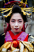 A portrait of a young Japanese woman dressed in traditional geisha robes in Fukuoka, Japan.