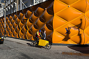 A cyclist courier pedals past a pedestrian beneath the temporary renovation hoarding of luxury brand Louis Vuitton in New Bond Street, on 25th February 2019, in London, England.