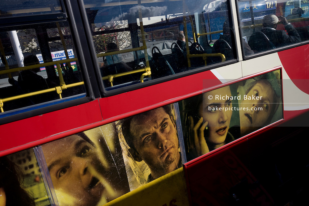 Faces of actors from the film Contagion adorn the upper deck of a red London double-decker bus.