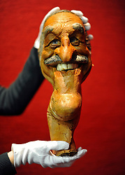 © Licensed to London News Pictures. 08/12/2011, London, UK. A Bonhams employee holds a puppet from satirical television programme Spitting Image of entertainer Bruce Forsyth.  The mask is expected to fetch 300-400 GBP.  Bonhams, London, photocall for entertainment memorabilia today, 8th December 2011.  The auction takes place on Thursday 15th December. Photo credit : Stephen Simpson/LNP