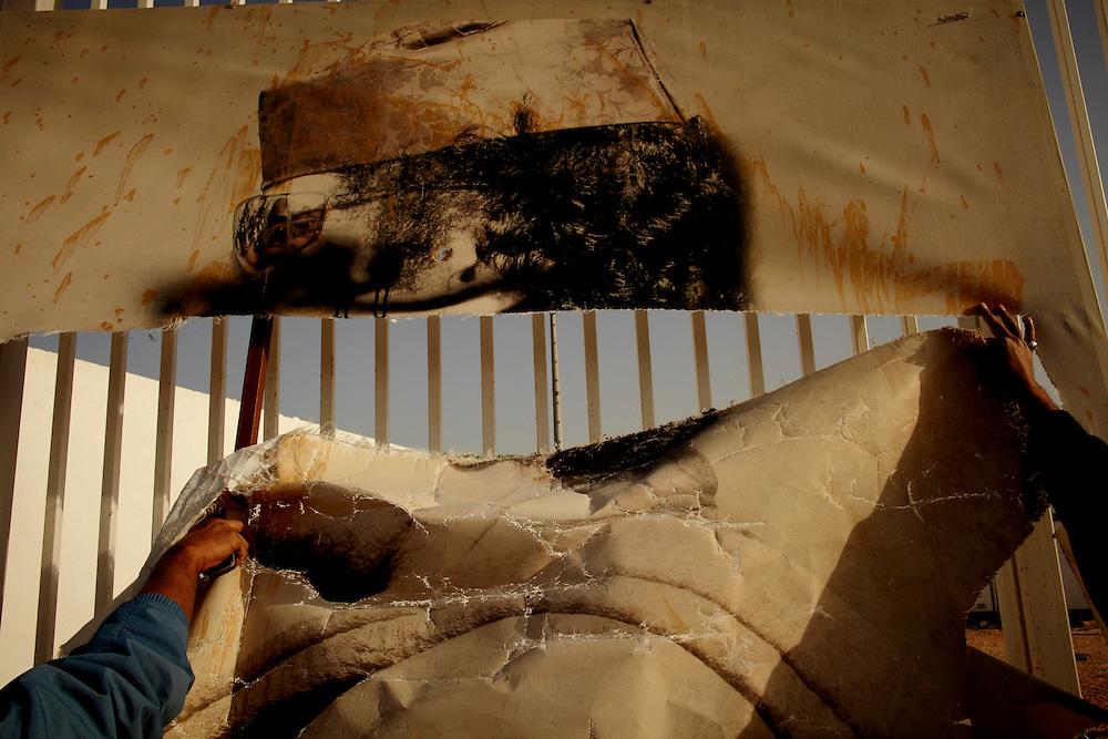 Benghazi, Libya, 01.03.11..En ødelagt poster av Ghadaffi utenfor Hugo Chavez Stadium..Foto: Eivind H. Natvig