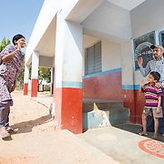 CAPTION: The Chamkol programme supports the government's response to the health and wellbeing of individuals with or at disk of disability. For Village Rehabilitation Workers (VRWs) like Rekha (who herself has polio) - pictured here visiting a boy with a learning disability who she recently supported in entering the formal education system - informal support to service delivery means provision of tailored quarterly training. LOCATION: Meghalahundi (village), Kasaba (hobli), Chamrajnagar (district), Karnataka (state), India. INDIVIDUAL(S) PHOTOGRAPHED: Rekha H.B. (woman), Mahesh (boy) and Mahadevaswamy (man).