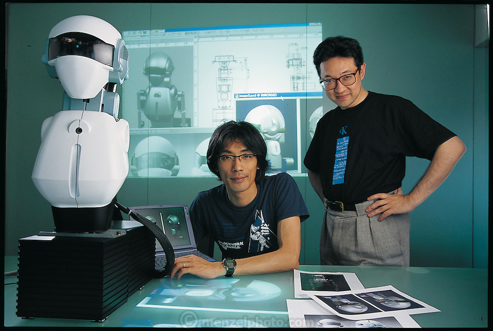 Surrounded by his plans and sketches, designer Tatsuya Matsui (seated) contemplates the next phase in the evolution of SIG, the robot under development by Hiroaki Kitano (standing). Kitano, a senior researcher at Sony Computer Science Laboratories, Inc. and director of this government-funded project, wants to endow SIG with sufficient eyesight, hearing, and processing power to follow instructions given by several people in a crowd. The goal is ambitious, but Kitano is well-placed to achieve it. In 1997, he created the now-famous RoboCup, in which robot teams from around the world meet every year to play soccer in an indoor arena. Japan. From the book Robo sapiens: Evolution of a New Species, page 83.
