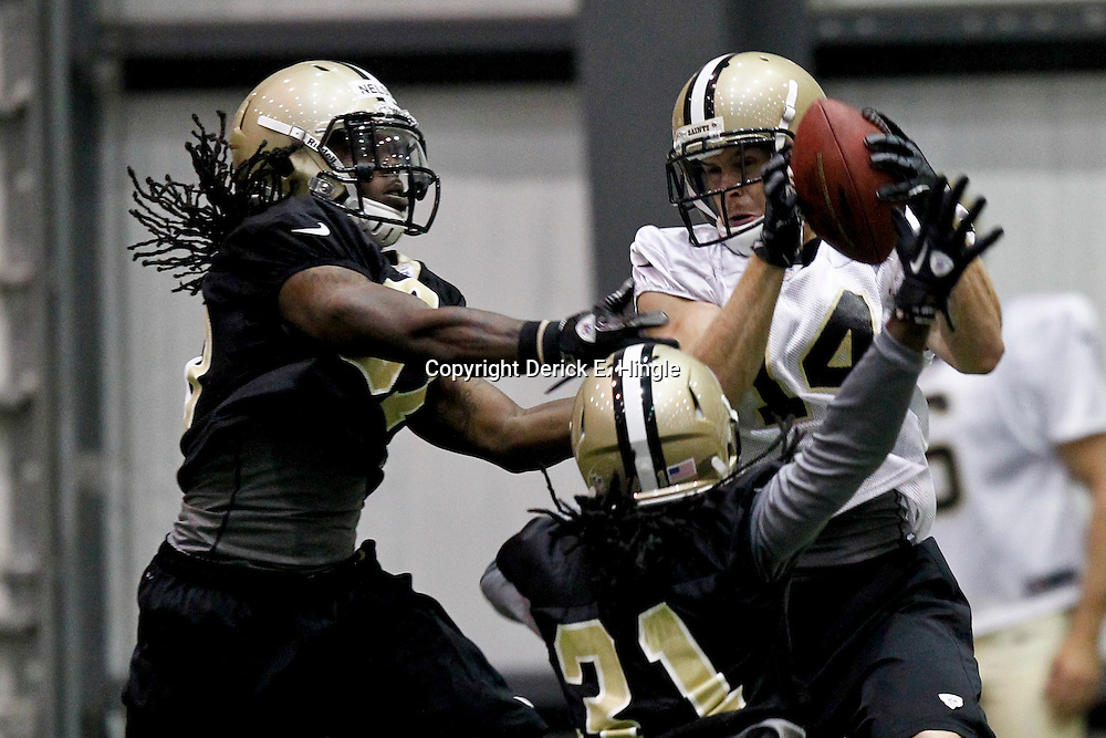 July 26, 2012; Metairie, LA, USA; New Orleans Saints wide receiver Andy Tanner (14) makes a reception between cornerback Cord Parks (31) and safety Jerico Nelson (37) during the first day of of training camp at the team's indoor practice facility. Mandatory Credit: Derick E. Hingle-US PRESSWIRE