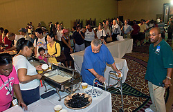 30 August, 2005. Aftermath of Hurricane Katrina, New Orleans, Louisiana. <br /> Hundreds of hotel refugees wait patiently in line for limited rationed meals at the Hyatt Hotel downtown.<br /> Photo Credit: Charlie Varley/varleypix.com