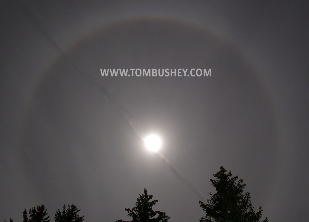 Middletown, NY - The condensation trail from a jet airplane cuts through a ring around the moon on the night of Oct. 13, 2008. The ring around the Moon is caused by the refraction of moonlight through ice crystals suspended in the upper atmosphere. A moon ring or moon halo will always be roughly the same size - 22-degrees across the sky - because the crystals bend the light at a 22-degree angle from their original path. The moon itself is overexposed in this 8-second image.