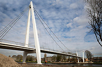 Dafne Schippersbrug tussen Oog en Al en Leidsche Rijn in Utrecht. Het fietspad in een slinger loopt over een school en sluit dan aan op de brug.