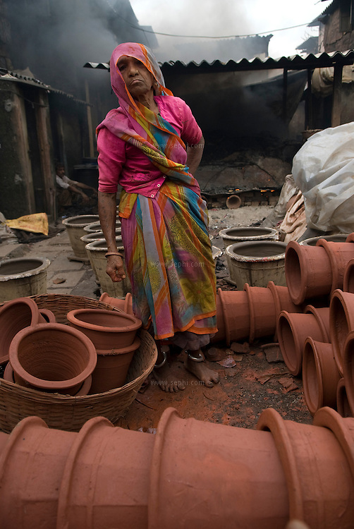 An old woman about to take her pots to the kiln. Dharavi, Mumbai August 2007