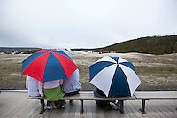 Tourists Waiting in Rain for Old Faithful Geyser Eruption, Yellowstone National Park, Wyoming