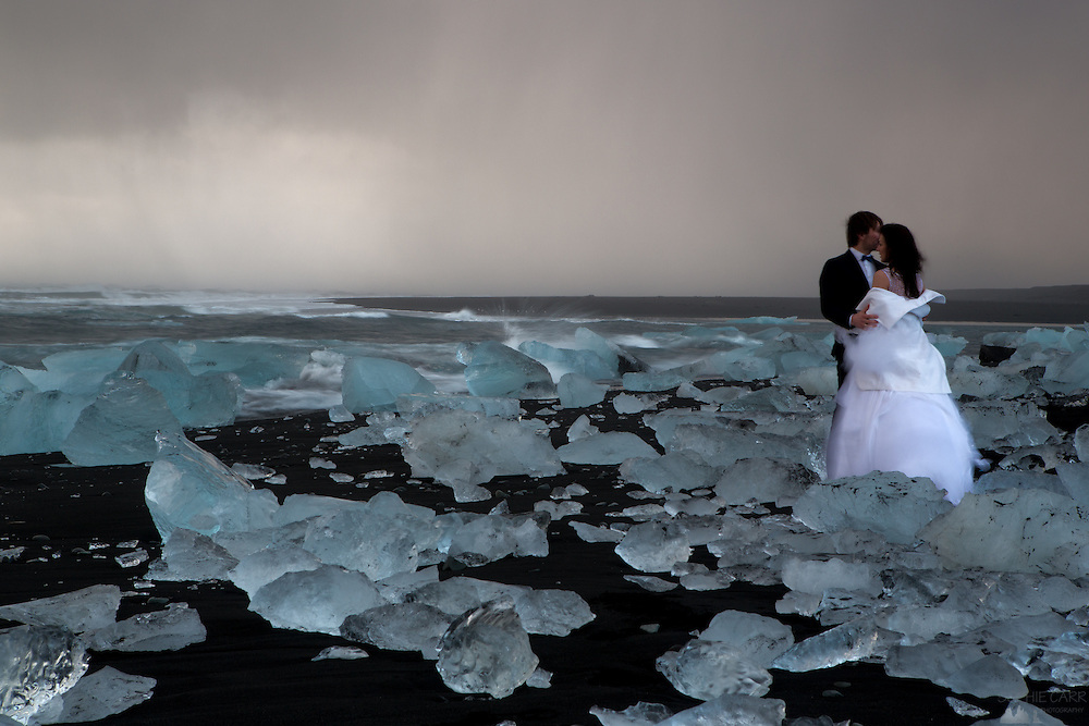 A couple braves the freezing wind and hail showers to get some wedding photos taken among the icebergs strewn on Jökulsárlón Beach