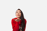 Portrait of woman in Christmas sweater blowing kiss over gray background