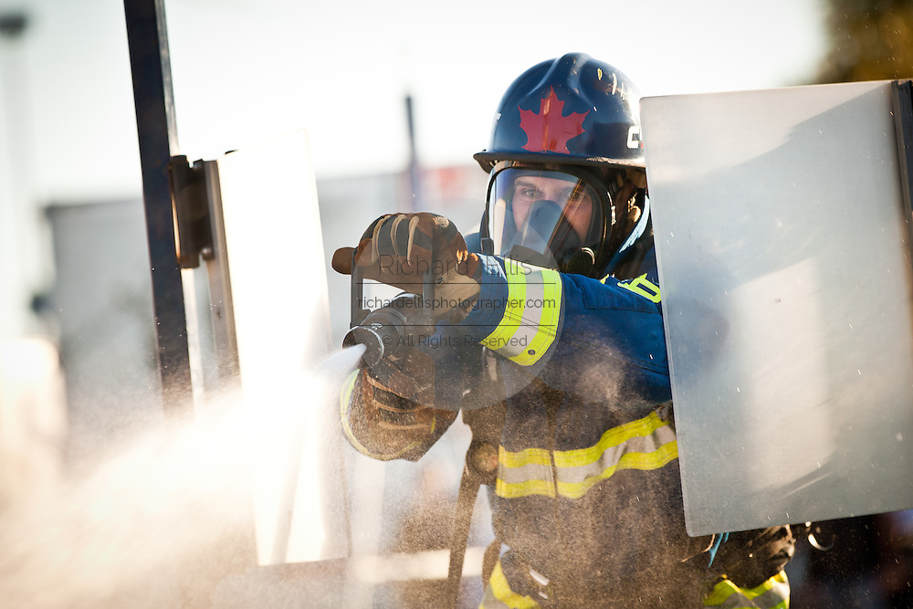 A firefighter from Canada aims a firehose at a target while wearing full firefighting gear and working against the clock during the international finals of the Firefighter Combat Challenge on November 18, 2011 in Myrtle Beach, South Carolina.