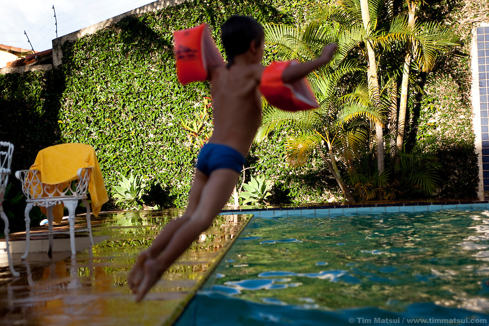 A young boy jumps into a backyard swimming pool with a pair of floatation water wings on for safety.