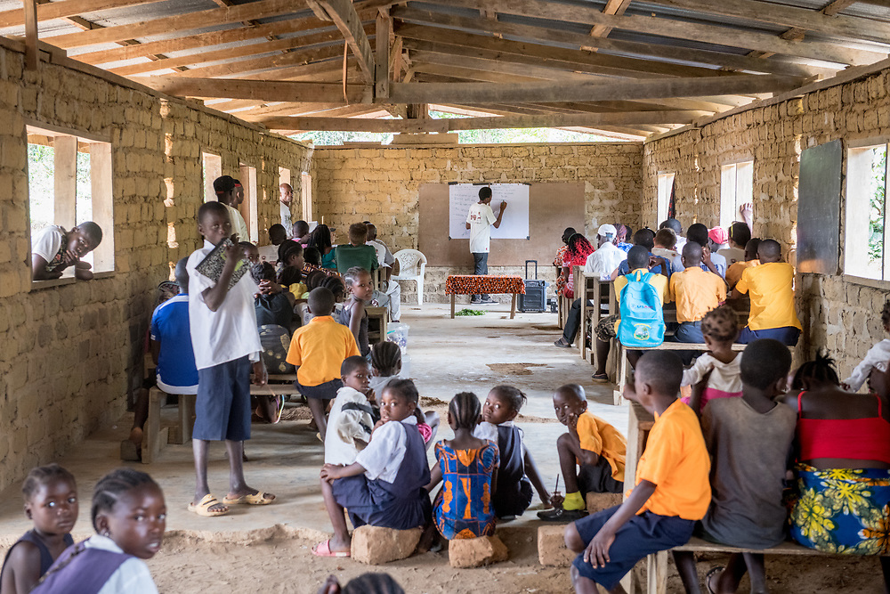 Adults and children pile in a classroom for a lesson in Ganta, Liberia