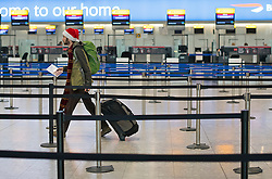 © Licensed to London News Pictures. 23/12/2016. London, UK.  A man wearing a santa hat walks through mpty check in isles at Heathrow Airport terminal 5, as the Christmas getaway begins, with stations, airports and roads expected to be very busy as people start their Christmas holidays. Photo credit: Ben Cawthra/LNP