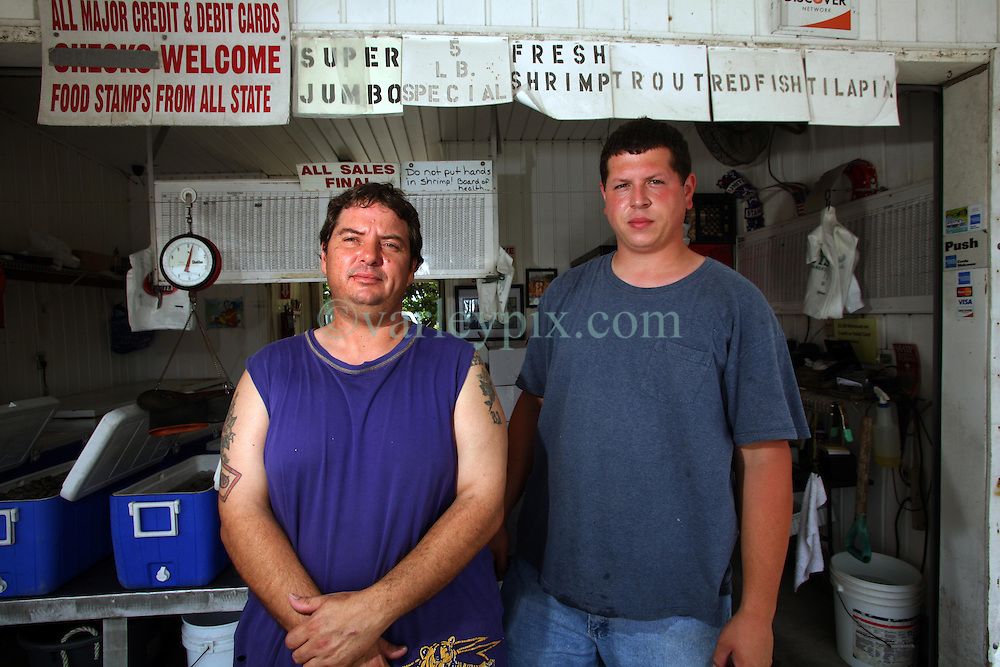 11june 2010. Westwego, Louisiana. <br /> Wayne Herbert (l) and his Lenny Cook, market traders  at the Shrimp Lot in Westwego just outside New Orleans.  Incomes have crashed as all seafood prices have risen over 30% in the past 4 weeks alone as stocks run low thanks to closed fishing grounds affected by oil pollution. BP's disastrous environmental catastrophe out in the Gulf of Mexico threatens  the livelihood of many thousands of workers affiliated to the fishing industry in Louisiana. Earnings are down as much as  50% of those pre BP's oil disaster. Thousands of barrels of oil per day continues to leak into the Gulf because of the explosion and collapse of the Deepwater Horizon drilling platform 46 miles out to sea. The closure of fishing grounds both east and west of the Mississippi river outflow is crippling thousands of local fishermen and all affiliated businesses and families who rely on the seafood industry. None of the shrimp or other seafood offered at the market are fresh catch from today. Everything has been through the IQF (Instant Quick Freeze) process and is seafood caught out of state or earlier in the season and brought from storage freezers in Venice and Grand Isle. Louisiana stocks are virtually non-existant. With few new catches, the market will be forced to rely on farmed shrimp shipped in from Texas and Georgia. Local traders refuse to stock Chinese import fish raised with growth hormones, pesticides, fungicides and other contaminants widely found in Chinese farm raised seafood. Many fear losing their jobs and everything they own as a result of BP's Gulf Coast environmental disaster.<br /> Photo; Charlie Varley/varleypix.com