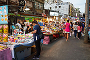Tourists and locals walk around Raohe night market in the early evening. The market is one of the most popular in Taipei, with a wide variety of street food, stalls and games available.