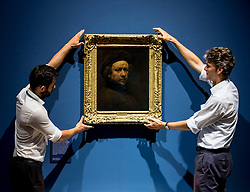 Senior Curator of Northern European Art with the 1national 1galleries of Scotland, Dr Tico Seifert (right)  puts the finishing touches to one of the priceless paintings by Rembrandt, assisted by gallery staff.<br /> <br /> &copy; Dave Johnston / EEm