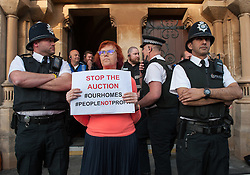 © Licensed to London News Pictures.20/04/2016. Bristol, UK.  A woman holds a placard in a police line at a protest while behind her potential buyers enter for an auction of council houses held at All Saints Church in Pembroke Road, Clifton, Bristol. Campaigners want the council to stop selling off 14 council homes on 20 April by auction to the private sector. Bristol City Council says the homes are expensive to repair, but some campaigners question whether the costs of repairs are inflated, and also whether the homes will be bought and then relet to the Council for temporary accommodation at higher than normal rents.  A group of residents of St. Paul's and the Inner City are campaigning against the sale. They are working in partnership with The Community Rights Project, The Bristol People's Assembly, and members of the ACORN community union. Photo credit : Simon Chapman/LNP