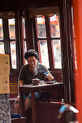 A Chinese man enjoys tea in the Huxinting Teahouse in Yu Yuan Gardens Shanghai, China